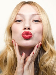 rby-holiday-makeup-woman-puckering-with-red-lip-mdn-73718200